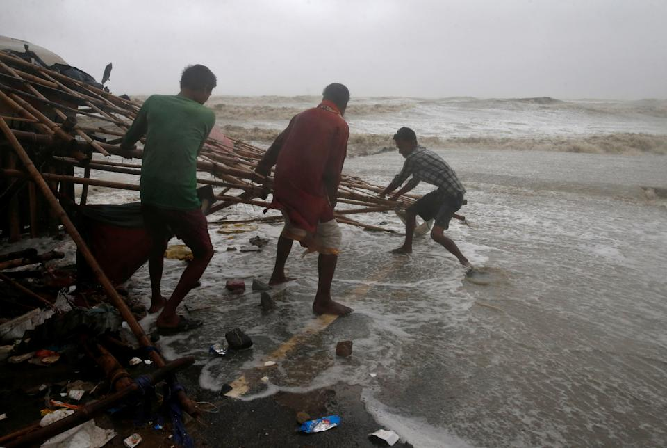 Men remove bamboo rooftop of a stall damaged by heavy winds at a shore ahead of Cyclone Yaas in Bichitrapur in Balasore district in the eastern state of Odisha India, May 26, 2021. REUTERS/Rupak De Chowdhuri