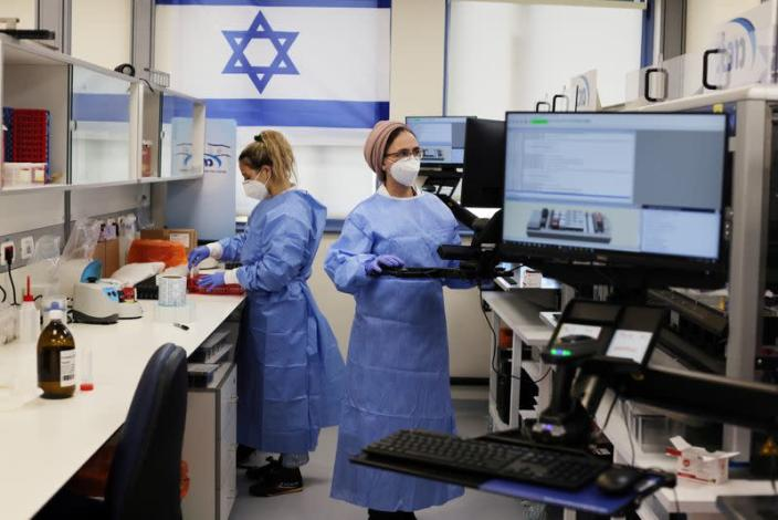 FILE PHOTO: Technicians work at Healthcare Maintenance Organization (HMO) Maccabi's coronavirus disease (COVID-19) public laboratory, performing diverse and numerous tests, in Rehovot