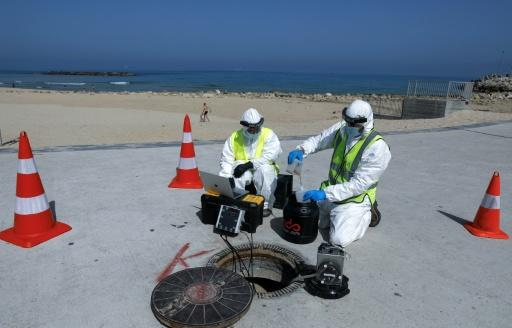 Technicians from Israeli firm Kando extract sewage samples from a manhole near the beach, in the southern coastal Israeli city of Ashkelon