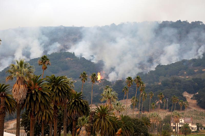 Smoke and flames rise as a wildfire from the Santa Rosa and Napa Valley moves through the area.