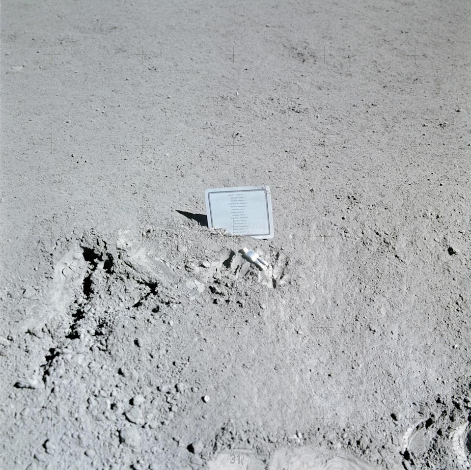 A small metal plaque stuck simply in moon dirt