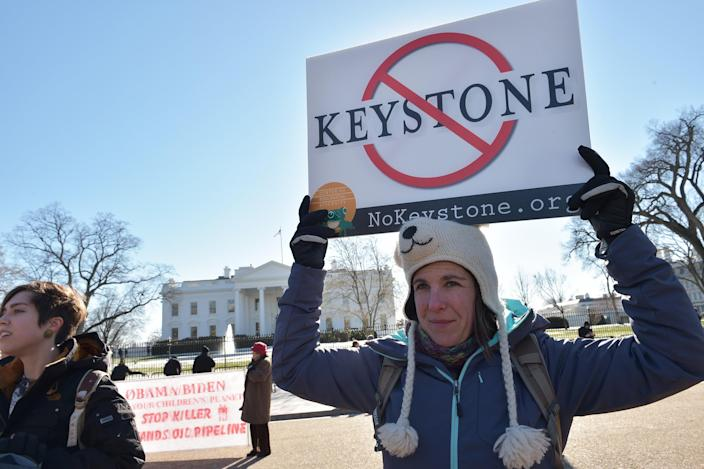 A woman holds a placard during a protest outside of the White House against the building of the proposed Keystone XL oil pipeline on January 10, 2015 in Washington, DC (AFP Photo/Mandel Ngan)