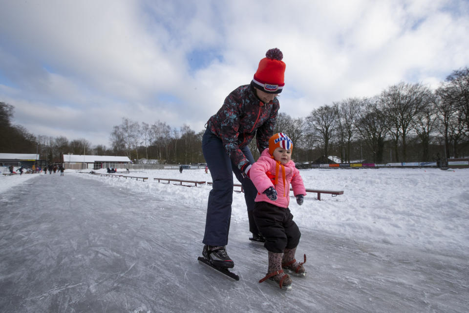 A mother teaches her daughter to skate on a rink in Doorn, Netherlands, Tuesday, Feb. 9, 2021. With freezing temperatures forecast for more than a week in the Netherlands, ice fever is sweeping the nation, offering a welcome respite from grim coronavirus news while also creating a challenge for authorities trying to uphold social distancing measures. (AP Photo/Peter Dejong)