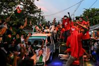 Supporters of the National League for Democracy in a motorcade pass supporters of the opposition Union Solidarity and Development Party during an election campaign event on the outskirts of Yangon