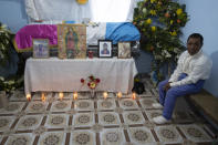A neighbor sits next to coffin with the remains of Rubelsy Tomas Isidro, one of the Guatemalan migrants who was killed near the U.S.-Mexico border in January, during a wake at his home in Comitancillo, Guatemala, Saturday, March 13, 2021. Thousands of residents of this Guatemalan town turned out Friday night amid tears and applause to receive the remains of 16 of their own, found piled in a charred pickup truck in Camargo, across the Rio Grande from Texas. (AP Photo/Moises Castillo)