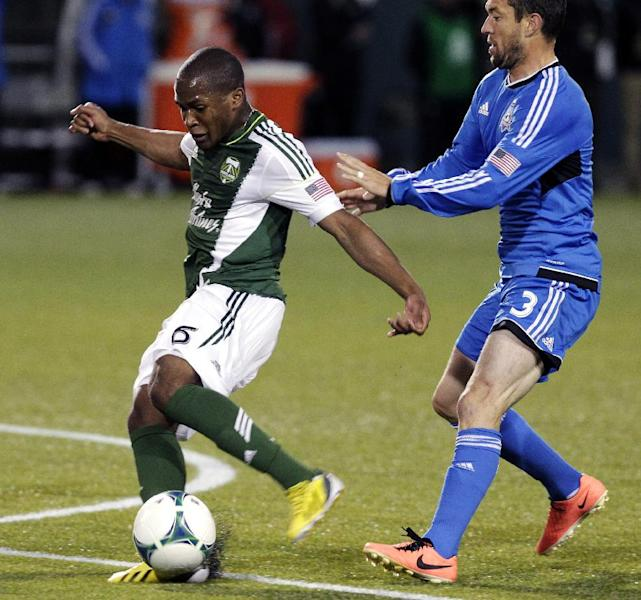 Portland Timbers midfielder Darlington Nagbe, left, takes a shot on goal against San Jose Earthquakes defender Dan Gargan during the first half of an MLS soccer match in Portland, Ore., Sunday, April 14, 2013. Nagbe did not score on the play. (AP Photo/Don Ryan)