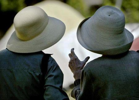 LADIES WEARING SUN HATS CHAT IN VANCOUVER PARK.