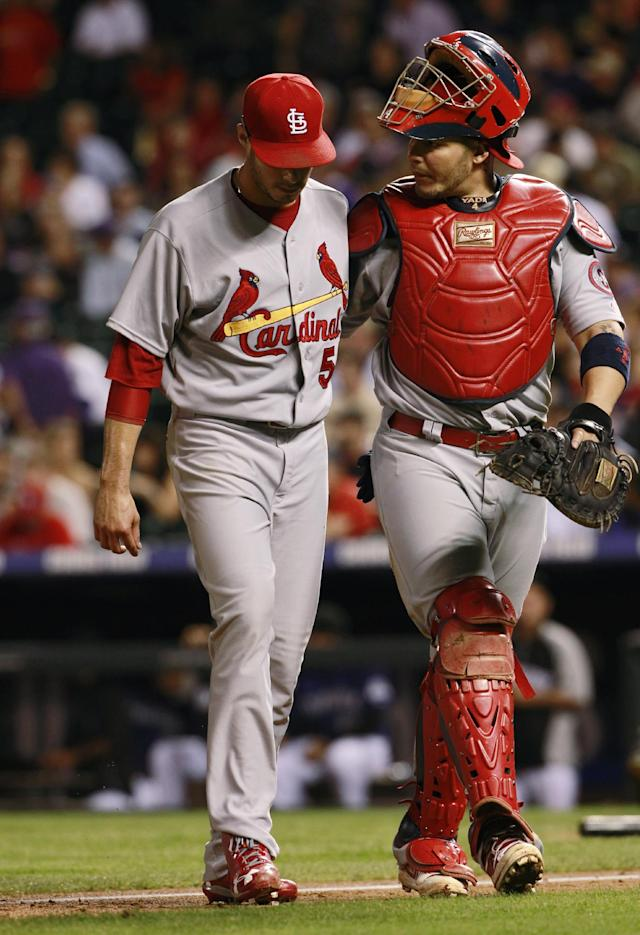 St. Louis Cardinals starting pitcher Joe Kelly, left, is hecked on by catcher Yadier Molina after Kelly retired the Colorado Rockies in the fifth inning of the Cardinals' 11-4 victory in a baseball game in Denver on Tuesday, Sept. 17, 2013. Kelly was injured while pitching to the Rockies' Corey Dickerson but remained on the mound to retire DJ LeMahieu for the final out in the fifth inning before being pulled from the game. (AP Photo/David Zalubowski)
