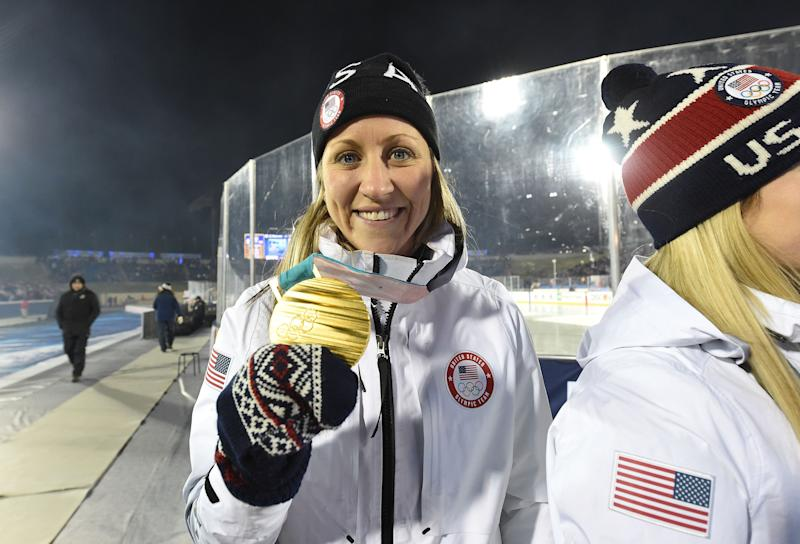 Meghan Duggan of the 2018 United States Women's Hockey Team holds up her gold medal during a ceremony.