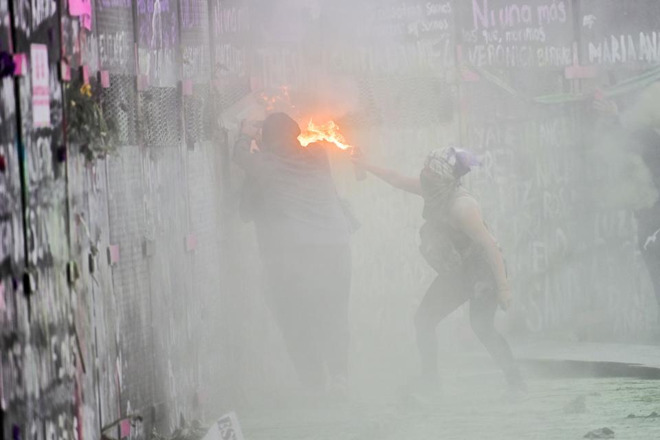 Women clash with the police, behind a fence in front of the National Palace, as they protest during a demonstration to commemorate the International Women's Day  in Mexico City, on March 8, 2021. (Photo by PEDRO PARDO / AFP) (Photo by PEDRO PARDO/AFP via Getty Images)