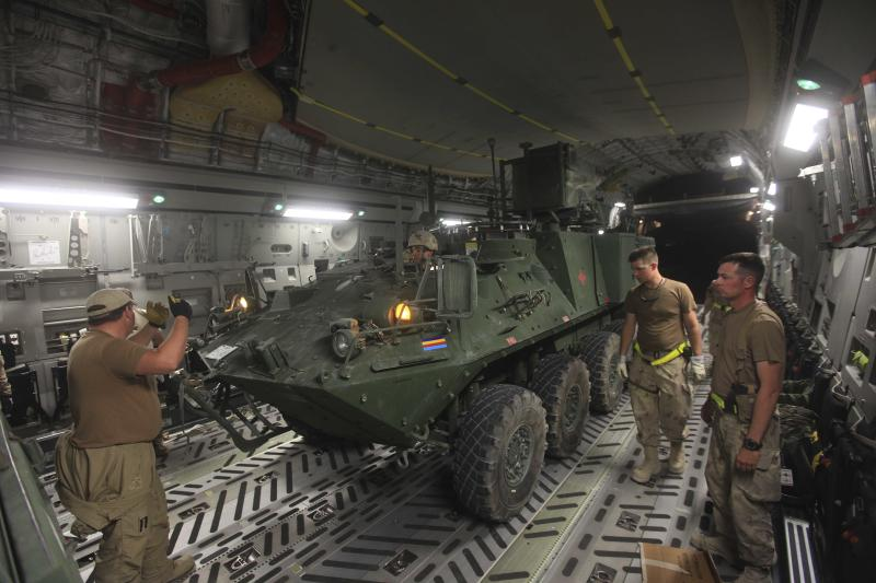 FILE - In this Saturday, July 16, 2011 file photo a Canadian armoured vehicle is loaded in a C-17 military transport aircraft at Kandahar airbase in Afghanistan. Canada withdrew 2,850 combat forces from Afghanistan this summer. (AP Photo/Rafiq Maqbool/file)