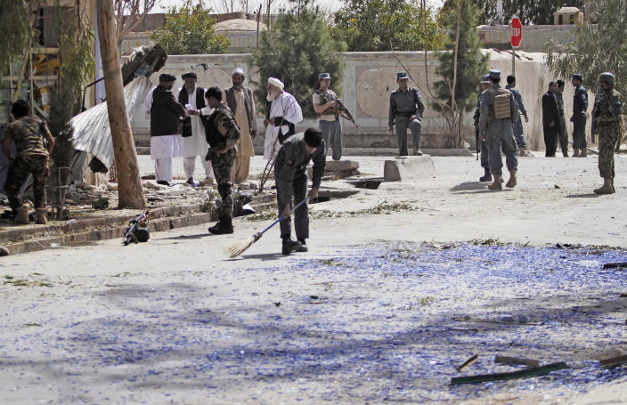 An Afghan policeman sweeps broken glass at the scene of a bomb explosion in Kandahar south of Kabul, Afghanistan, Wednesday, March 14, 2012. A delegation investigating Sunday's shooting killing civilians in Panjwai, Kandahar by a U.S. soldier was meeting in the southern city of Kandahar on Wednesday when a bomb hidden in a motorcycle exploded about 600 yards away. The blast killed one Afghan intelligence official and wounded three other people, but the delegation members were unharmed. (AP Photo/Allauddin khan)