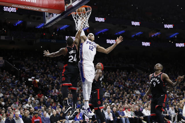 Philadelphia 76ers' Tobias Harris (12) goes up for a shot against Toronto Raptors' Norman Powell (24) during the second half of an NBA basketball game, Sunday, Dec. 8, 2019, in Philadelphia. (AP Photo/Matt Slocum)
