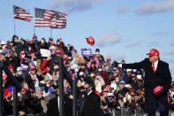 President Donald Trump throws hats to supporters as he arrive to speak during a campaign rally at Wilkes-Barre Scranton International Airport, Monday, Nov. 2, 2020, in Avoca, Pa. (AP Photo/Evan Vucci)