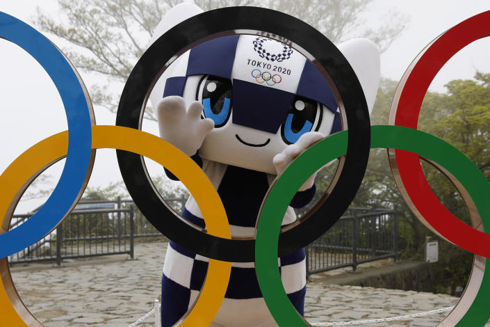 FILE - In this April 14, 2021, file photo, Tokyo 2020 Olympic Games mascot Miraitowa poses with a display of Olympic Symbol after an unveiling ceremony of the symbol on Mt. Takao in Hachioji, west of Tokyo to mark 100 days before the start of the Olympic Games. Japan is set to raise the coronavirus alert level in Tokyo's three neighboring prefectures and a forth area in central Japan to allow tougher measures as a more contagious coronavirus variant spreads and doubts are growing whether the Olympics can go ahead. (Kim Kyung-Hoon/Pool Photo via AP)