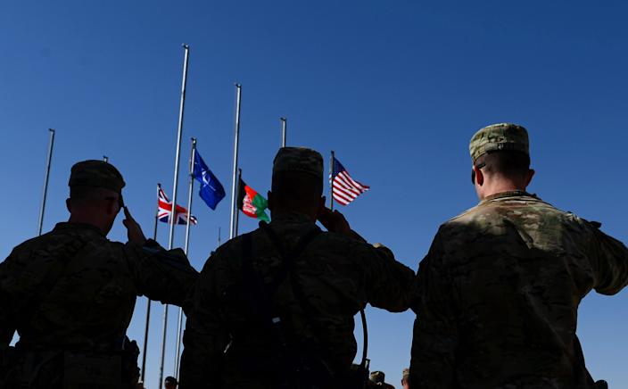 Soldiers salute as the British, NATO, Afghan, and US flags are lowered before the troop withdrawal from Camp Bastion-Leatherneck at Lashkar Gah in Helmand province on October 26, 2014 (AFP Photo/Wakil Kohsar)