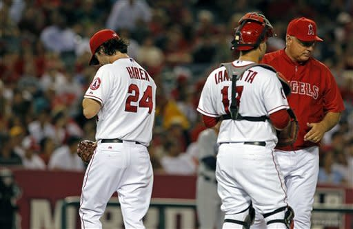 Los Angeles Angels pitcher Dan Haren (24) comes out of the game as manager Mike Scioscia and catcher Chris Iannetta wait for a reliever in the fourth inning of a baseball game against the Tampa Bay Rays in Anaheim, Calif., Thursday, Aug. 16, 2012. (AP Photo/Reed Saxon)