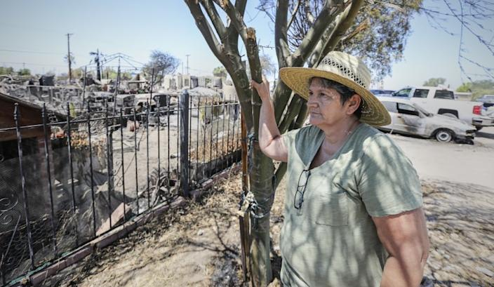 "Ana Valenzuela stares at the pile of ashes and debris where her home in Niland, Calif., once stood. <span class=""copyright"">(Eduardo Contreras / San Diego Union-Tribune)</span>"