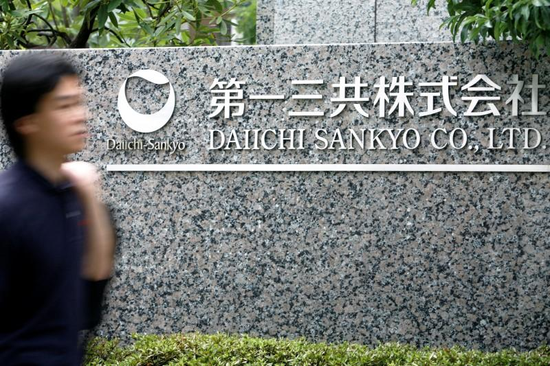 FILE PHOTO: A man walks past a sign of Japanese pharmaceutical company Daiichi Sankyo Co., Ltd. at the company's head office in Tokyo