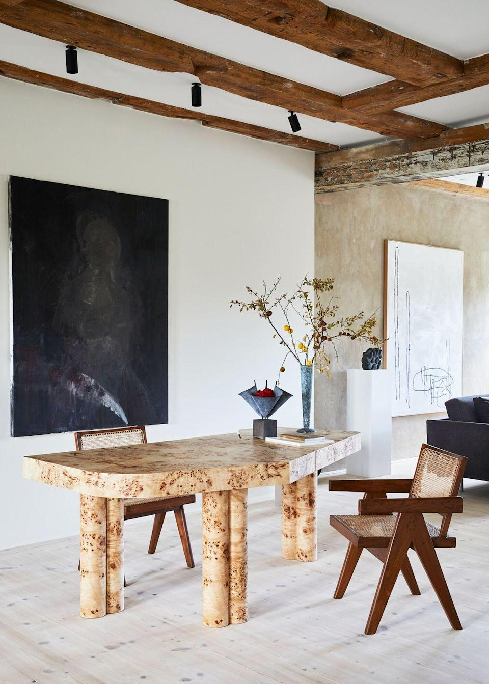 <p>Install track lighting to clear up space on the desk that you'd use for task lighting so you can really spread out as you work. We love how the rustic farmhouse bones of the space feel like a natural fit with the rest of the environment even though the furniture and artwork are super modern. This is thanks to the organic materials, like burled wood and rattan. </p>