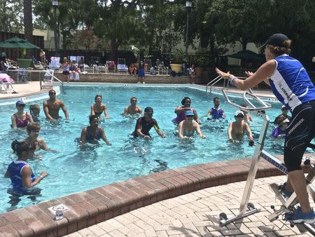 Participants take part in a Hydrorider aqua cycling class in this handout photo provided by Hydrorider at a fitness conference in Tampa, Florida, May 14, 2014. REUTERS/Andrea Wilson/Hydrorider/Handout via Reuters