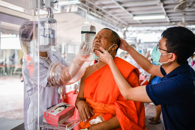 BANGKOK, THAILAND - 2020/05/30: A health worker collects a nasal swab sample from a Thai Buddhist monk to test for COVID-19 coronavirus at Wat Pho Temple in Bangkok. The Ministry of Public Health of Thailand has recorded 3,081 coronavirus cases, 2,963 recovered and 57 dead. (Photo by Amphol Thongmueangluang/SOPA Images/LightRocket via Getty Images)