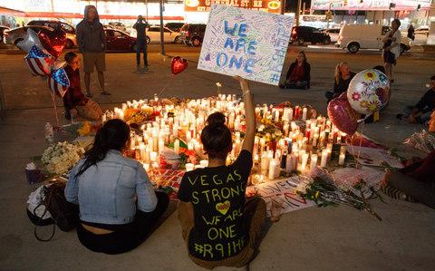 Mourners pay tribute to Paddock's victims at a makeshift memorial on the Las Vegas Strip on October 2 - Credit: EPA/EUGENE GARCIA