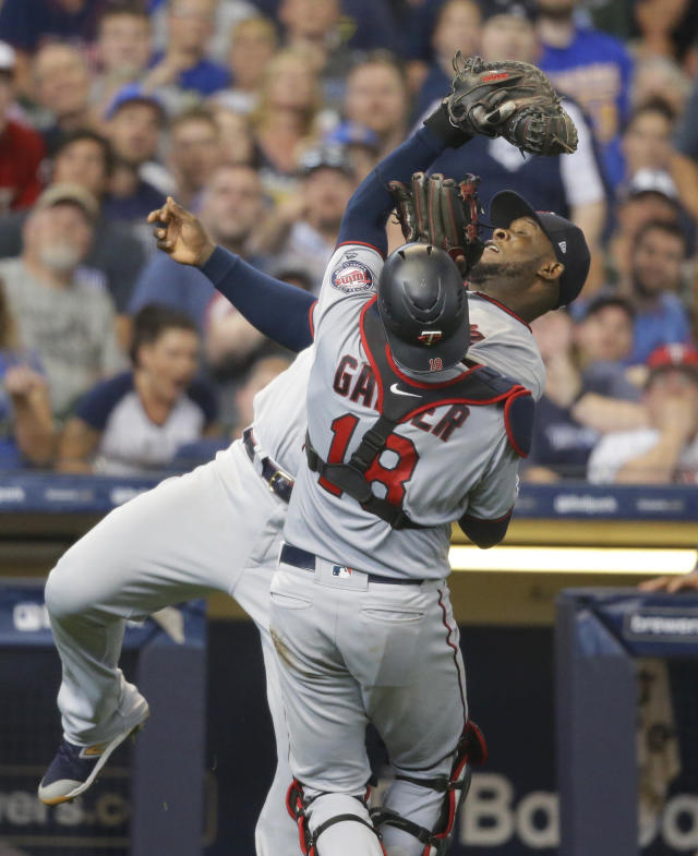 Minnesota Twins catcher Mitch Garver catches a foul ball from Milwaukee Brewers' Eric Thames as third baseman Miguel Sano almost collides with Garver during the seventh inning of a baseball game Wednesday, Aug. 14, 2019, in Milwaukee. (AP Photo/Jeffrey Phelps)