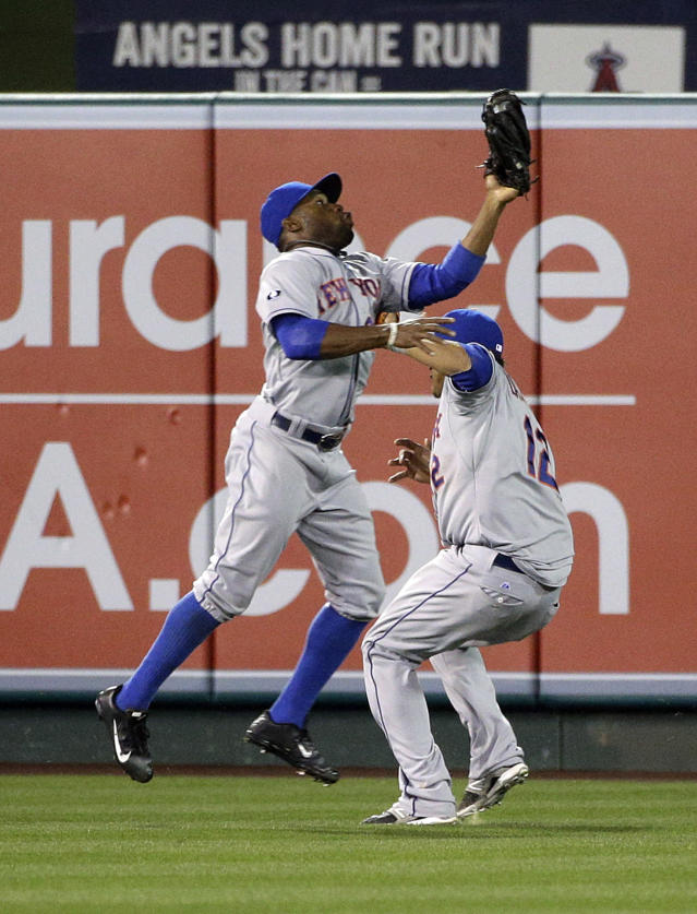 New York Mets' Eric Young Jr., left, catches a ball hit by Los Angeles Angels' Mike Trout as Juan Lagares avoids a collision during the fifth inning of a baseball game on Friday, April 11, 2014, in Anaheim, Calif. (AP Photo/Jae C. Hong)