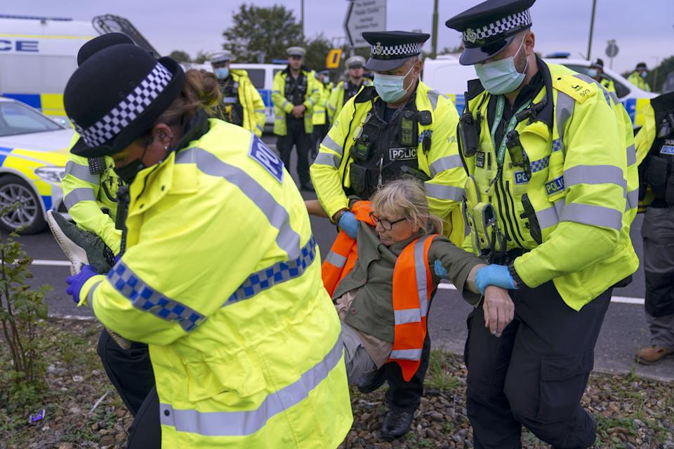 Police officers carry away a protester who had glued herself to a slip road at Junction 4 of the A1(M), near Hatfield, where climate activists carried out a further action after demonstrations which took place last week across junctions in Kent, Essex, Hertfordshire and Surrey. Picture date: Monday September 20, 2021.