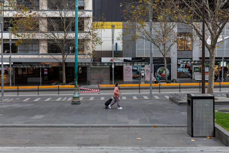 A lone shopper walks along a quiet Swanston Street in Melbourne, Australia: Getty Images