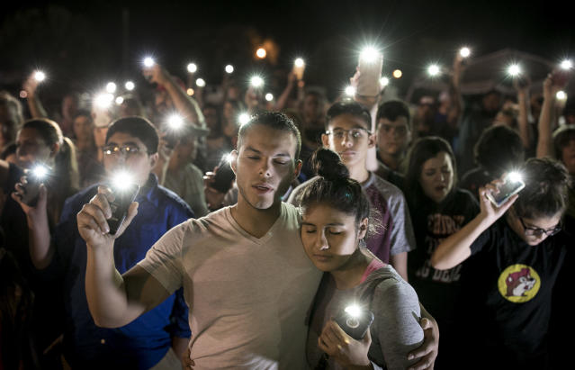 <p>Matthew Mata and Erika Gonzalez participate in a memorial service for the victims of Sunday's church shooting in Sutherland Springs, Texas, Monday, Nov. 6, 2017. The gunman of the deadly shooting had a history of domestic violence and sent threatening text messages to his mother-in-law, a member of First Baptist, before the attack in which he fired at least 450 rounds at helpless worshippers, authorities said Monday. (Photo: Jay Janner/Austin American-Statesman via AP) </p>