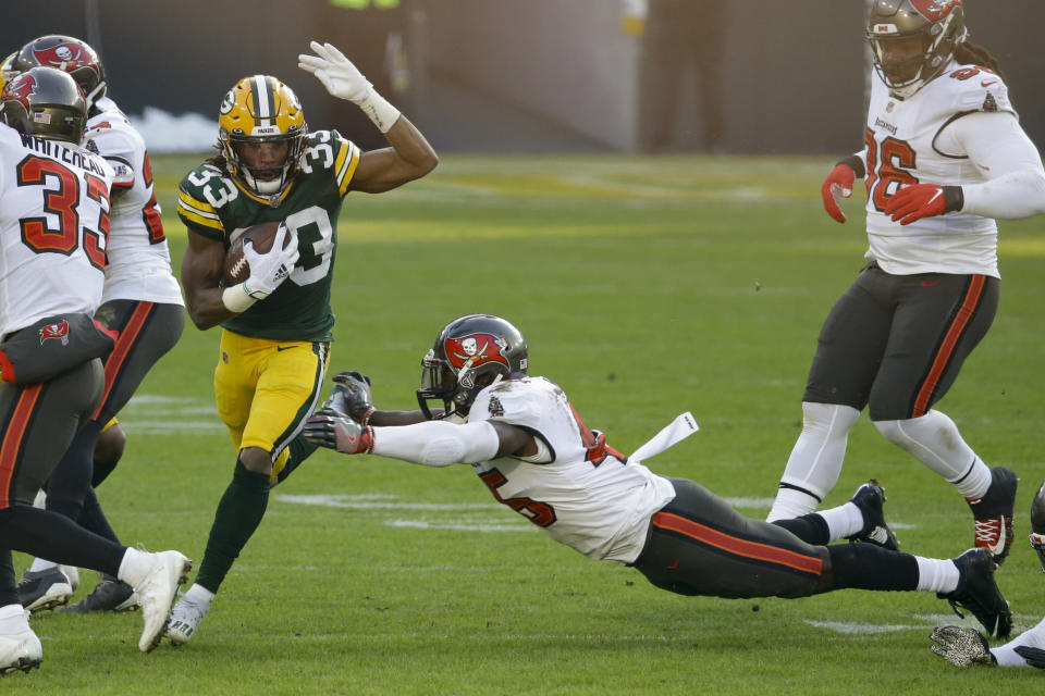 Green Bay Packers' Aaron Jones (33) evades a tackle from Tampa Bay Buccaneers' Lavonte David (54) during the first half of the NFC championship NFL football game in Green Bay, Wis., Sunday, Jan. 24, 2021. (AP Photo/Mike Roemer)