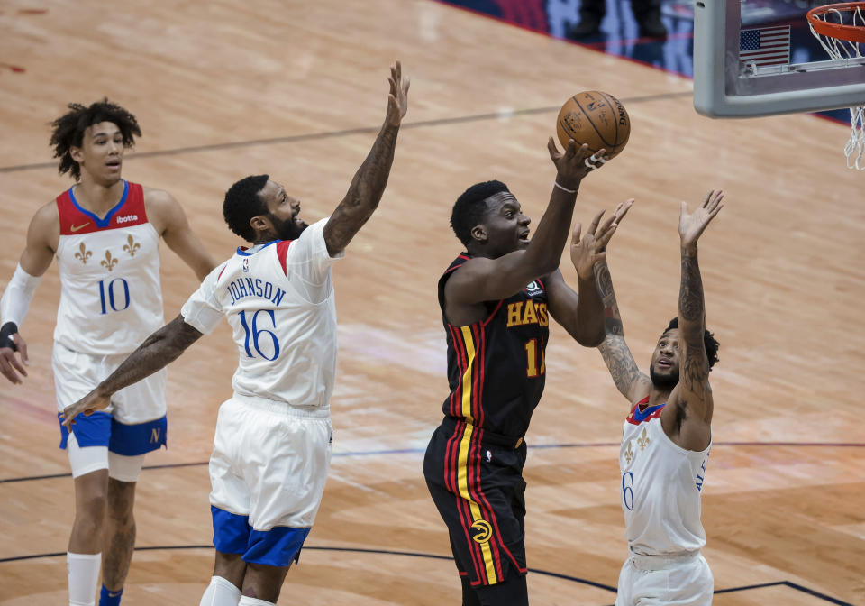 Atlanta Hawks center Clint Capela (15) shoots over New Orleans Pelicans guard Nickeil Alexander-Walker (6) and forward James Johnson (16) in the first quarter of an NBA basketball game in New Orleans, Friday, April 2, 2021. (AP Photo/Derick Hingle)