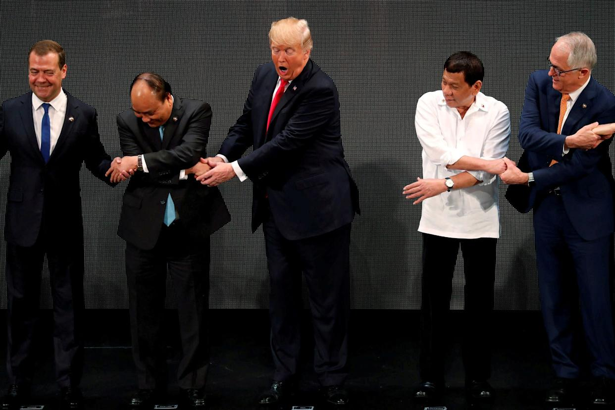 """Trump registers his surprise as herealizes other leaders, including Russia's Prime Minister Dmitry Medvedev, Vietnam's Prime Minister Nguyen Xuan Phuc, President of the Philippines Rodrigo Duterte and Australia's Prime Minister Malcolm Turnbull, are crossing their arms for the traditional """"ASEAN handshake"""" as he participates in the opening ceremony of the ASEAN Summit in Manila, Philippines,on Nov. 13."""
