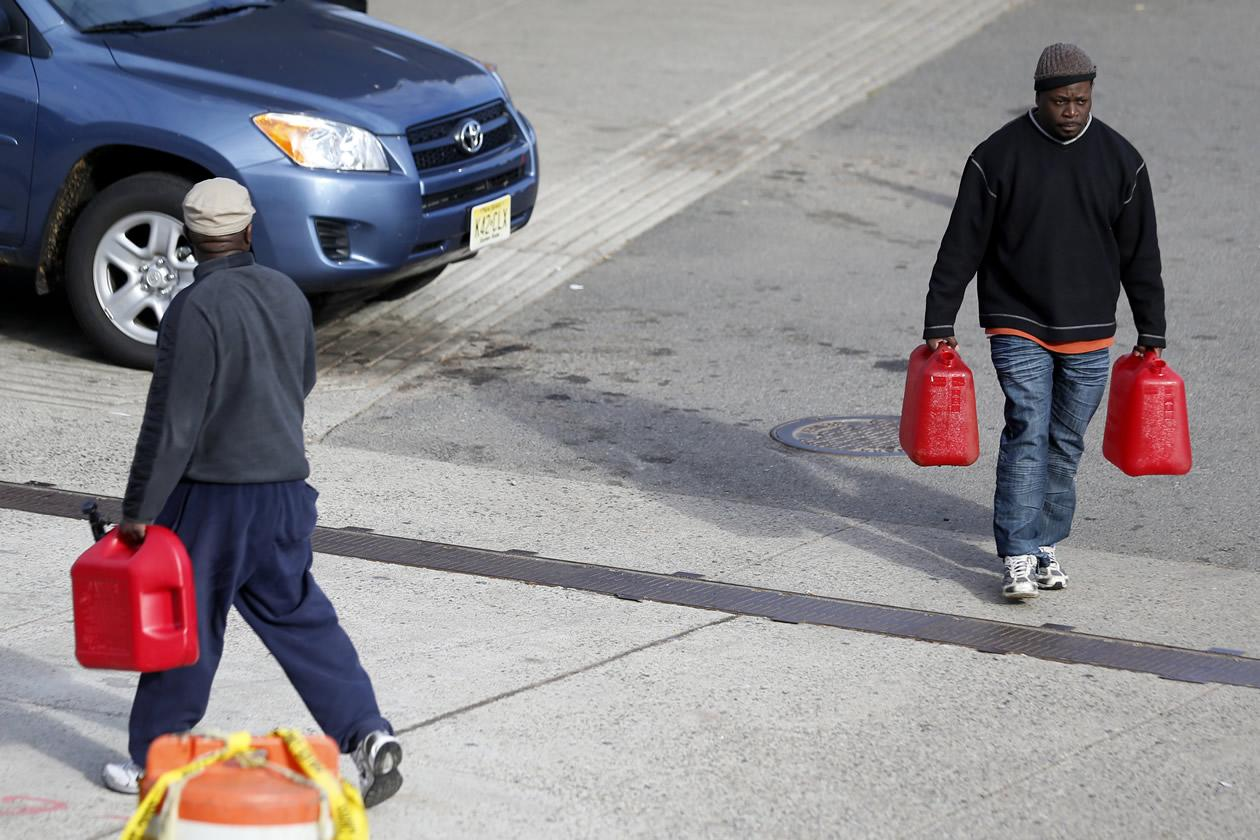 Richard Gardner, right, walks away from a pump after filling up a container as a man walks toward the beginning of the line at a gas station in Newark, N.J.