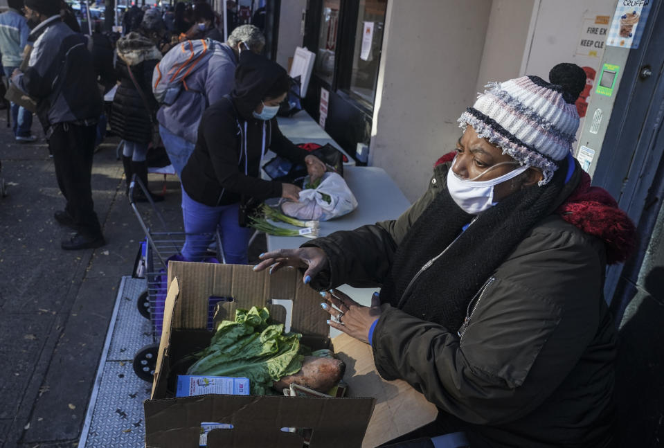 """Gloria Robinson, right, pack the last of items of food received at Harlem's Food Bank For New York City, a community kitchen and food pantry, Monday, Nov. 16, 2020, in New York. Robinson, who traveled from the nearby Bronx, said """"this is going to help a whole lot. I so appreciate it, I'm so happy right now."""" (AP Photo/Bebeto Matthews)"""