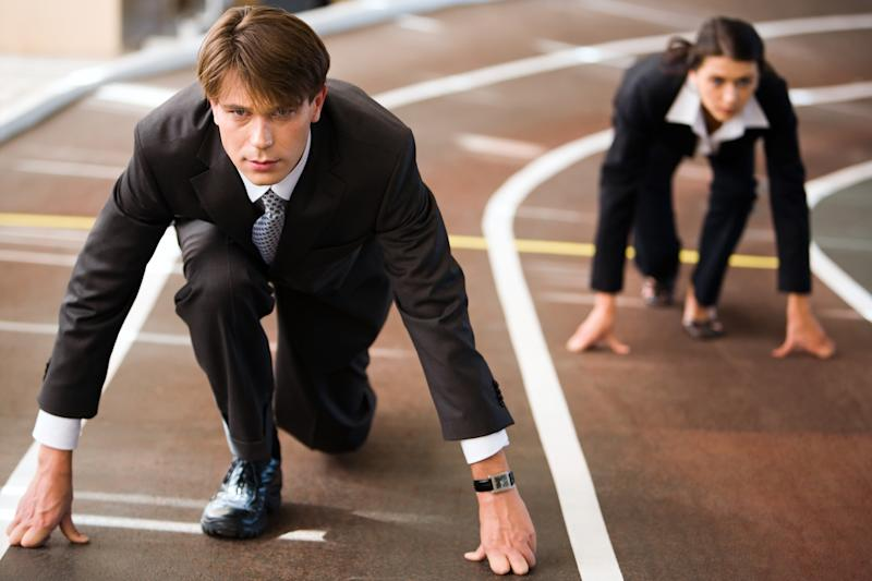 A man and a woman, dressed in dark business attire, in starting positions on a running track.