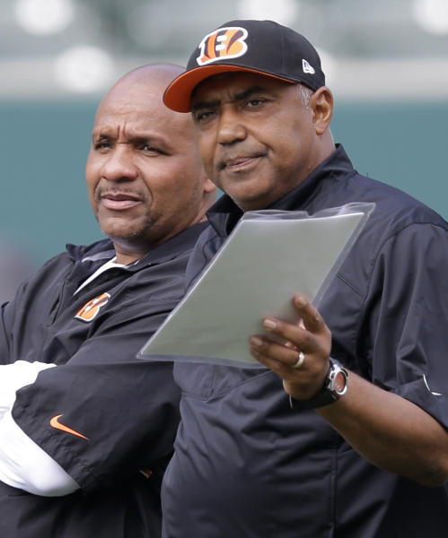 FILE - In this June 3, 2014, file photo, Cincinnati Bengals head coach Marvin Lewis, right, talks with then-offensive coordinator Hue Jackson during an NFL football organized team activity, in Cincinnati. Jackson needed only a few weeks to land another job in the place where he's always welcomed. The Bengals hired Jackson on Tuesday, Nov. 13, 2018, as a special assistant to head coach Marvin Lewis as he tries to resurrect Cincinnati's historically bad defense. Jackson was fired by the Cleveland Browns last month after he won only three games in three seasons as head coach.(AP Photo/Al Behrman, File)