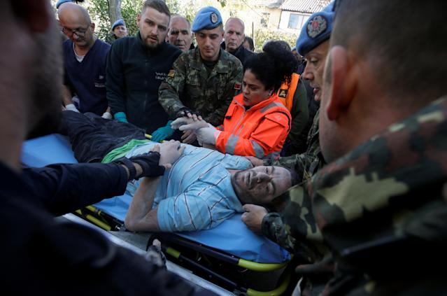 Military and emergency personnel help an injured man in Thumane. (Photo: Florion Goga/Reuters)