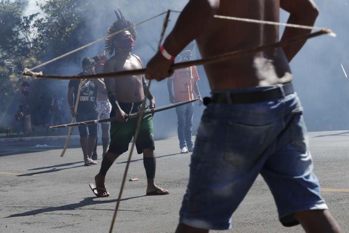Indigenous armed with bows and arrows clash with police during a protest opposing a proposed bill the Indigenous protesters say would limit recognition of reservation land, outside Congress in Brasilia, Brazil, Tuesday, June 22, 2021. (AP Photo/Eraldo Peres)