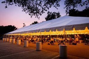 About half of the Westmont Orchestra can safely practice at a time under the big tent. Musicians are six feet apart and masked. Their brass and woodwind instruments are fitted with bell covers.