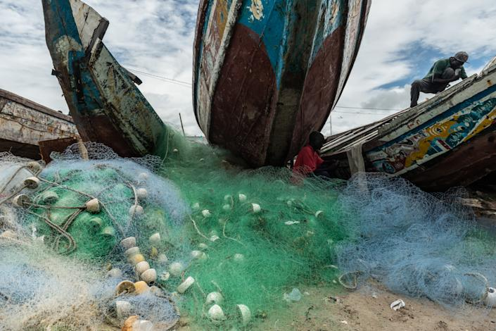 A pile of fishing nets next to Gambian fishermen and their vessels. (Fábio Nascimento / The Outlaw Ocean Project)