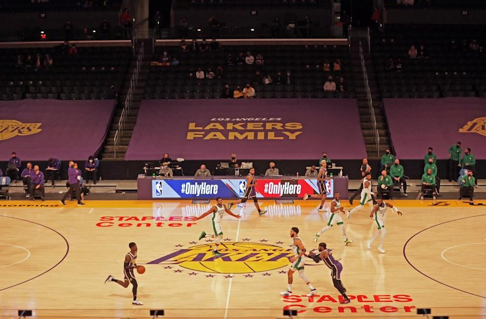 The Lakers and Celtics begin their game Thursday, with some fans in the stands at Staples Center.