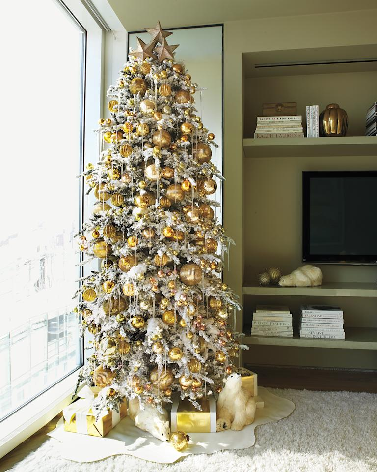 """<p>Kevin Sharkey punctuated this 10-foot-high flocked tree with golden glass balls, then added new and vintage glass icicles. Cut felt serves as a tree-skirt-cum-snowdrift.</p><p>Pre-lit heavy flocked spruce (similar to shown), 9', $485, <a href=""""http://homedepot.com"""" target=""""_blank"""" rel=""""noopener"""">homedepot.com</a>.</p>"""