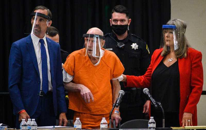 Joseph James DeAngelo (centre) and his public defenders Joseph Cress (left) and Diane Howard (right) wear face shields as they stand as Sacramento Superior Court.