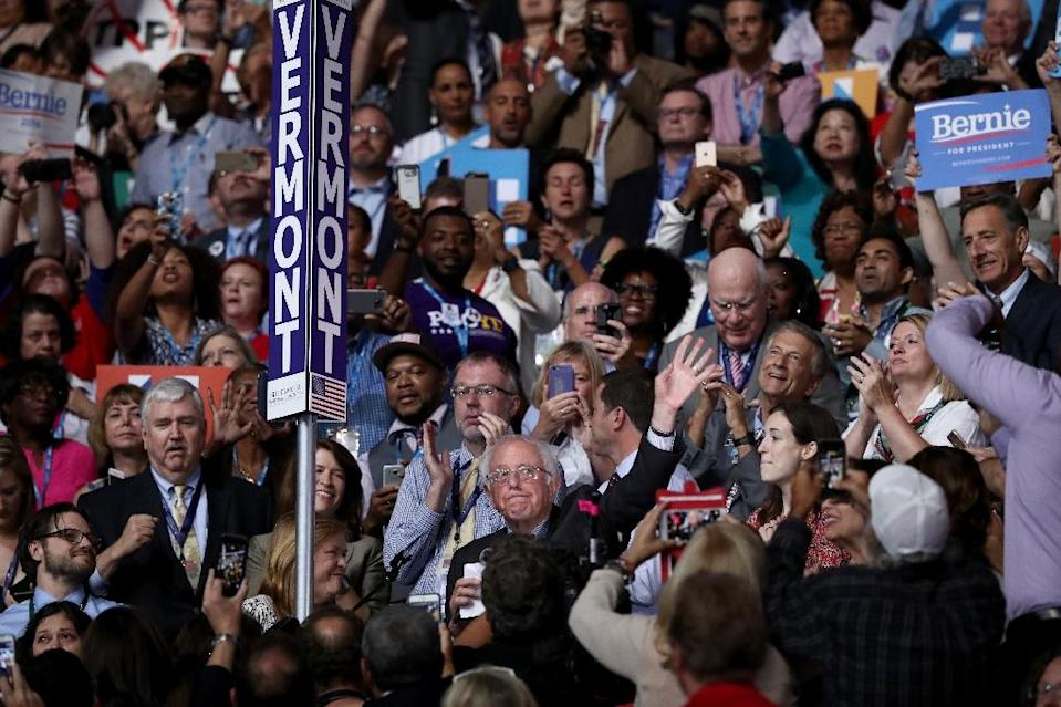 Senator Bernie Sanders (R) waves to the crowd after the Vermont delegation cast their votes during roll call on the second day of the Democratic National Convention in July 2016 (AFP Photo/Jessica Kourkounis)