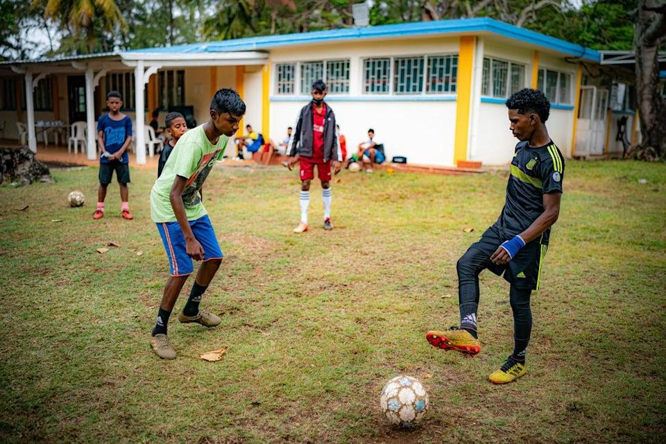 Young footballers pass the ball around during a coaching session at a training hub in Mauritius, where youngsters are given free sports training and coaching to help them pursue a career in professional sport (Ben Birchall/PA) (PA Wire)