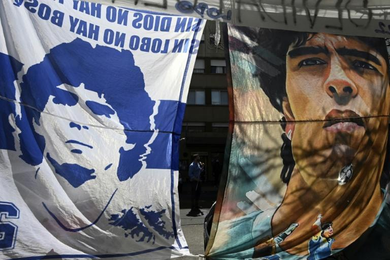 Flags bearing the image of Argentine football legend Diego Maradona hang outside a clinic in La Plata, where the 60-year-old was admitted on Monday