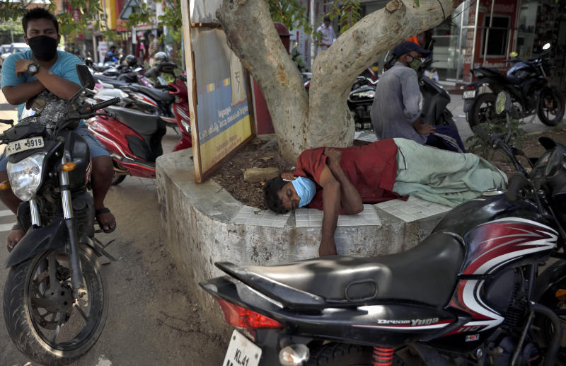 A man sleeps wearing a face mask beneath a tree by the side of a road during the coronavirus pandemic in Kochi, Kerala state, India, Saturday, May 30, 2020. (AP Photo/ R S Iyer)